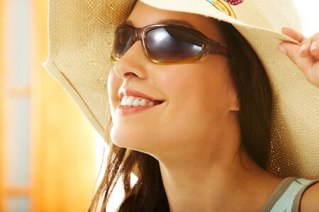 Portrait of happy girl in hat looking through sunglasses photo
