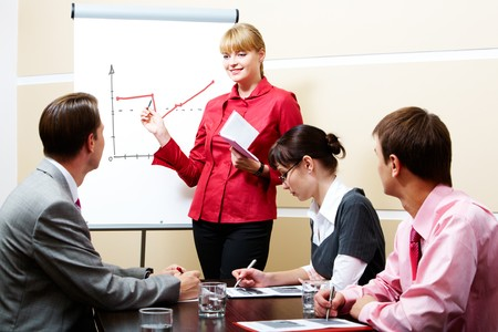 place of work: smart woman pointing at whiteboard at seminar while business partners listening to her Stock Photo