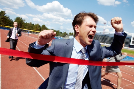 Photo of happy businessman crossing finish line during race  photo