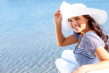 Portrait of pretty young lady in hat enjoying summer vacation photo