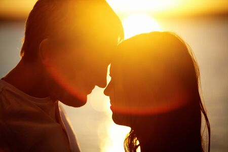 romantic: Profiles of romantic couple looking at each other on background of sunset