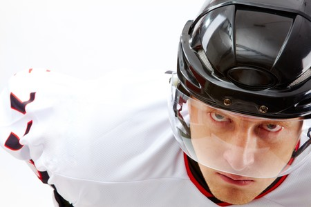 Portrait of sportsman in hockey uniform looking at camera with severe expression photo