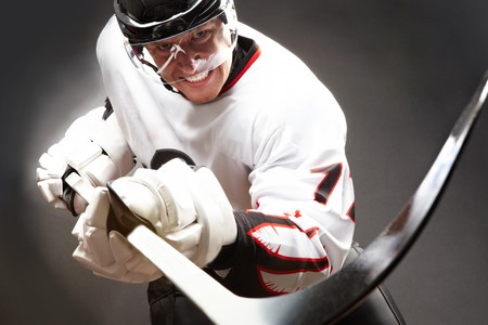 hockey player: Hockey player with cruel facial expression pointing stick into camera Stock Photo