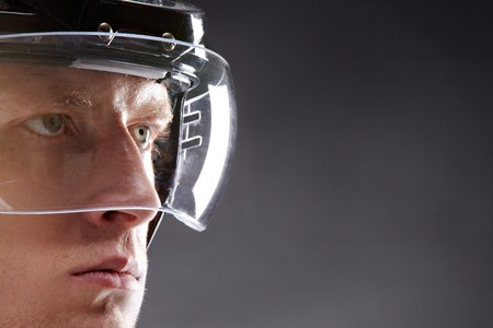Face of sportsman in protective helmet looking seriously forwards Stock Photo