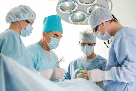 physicals: Several surgeons surrounding patient on operation table during their work Stock Photo