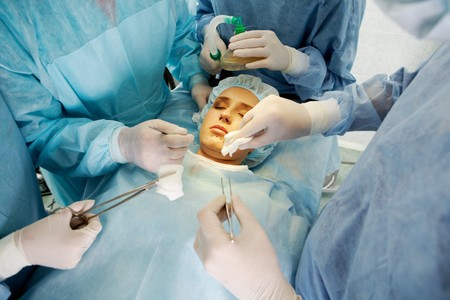 nose close up: Photo of young female patient lying with closed eyes before operation with hands of doctors over her