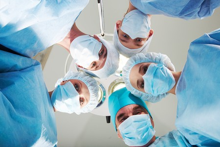 physicals: View of doctors by patient after operation on background of lamp and ceiling Stock Photo
