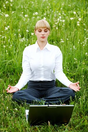 Portrait of businesswoman sitting on the grass and meditating photo