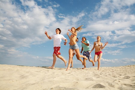 dinamismo: felici amici in esecuzione sulla spiaggia di sabbia in estate  Archivio Fotografico