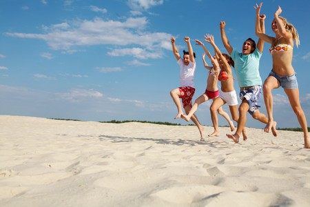 happy friends running down sandy beach with raised arms photo