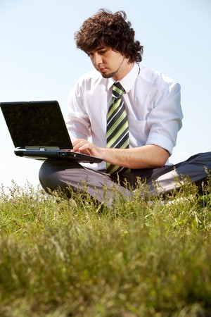 Portrait of serious businessman looking at the laptop in a natural environment   photo