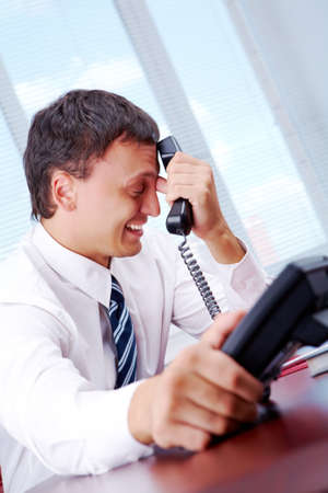 Portrait of frustrated employer with phone receiver at workplace Stock Photo - 7300043