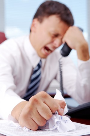 the boss: Suffering businessman crumpling document while holding phone receiver Stock Photo