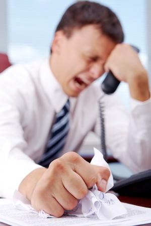 jefe enojado: Sufrimiento crumpling de documento de empresario mientras mantiene el tel�fono receptor