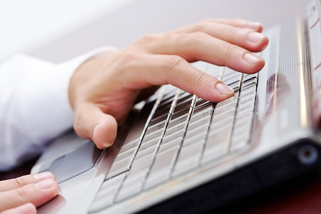 Close-up of male hand touching button of silver laptop keyboard photo