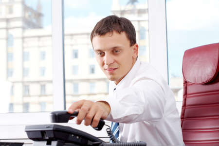 smart businessman putting phone receiver on its place in office after conversation Stock Photo - 7300057