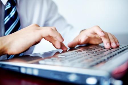 klawiatura: Biznesmen wpisywanie na jego komputerze przenoÅ›nym