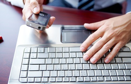 businessman phone: Close up image of male hands working on laptop and cell phone Stock Photo