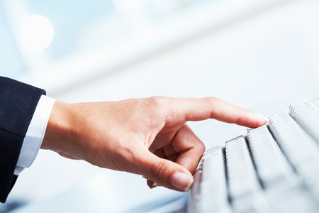 Close-up of female forefinger on button of white computer keyboard photo