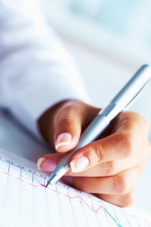 Close-up of business person hand with pen over paper photo