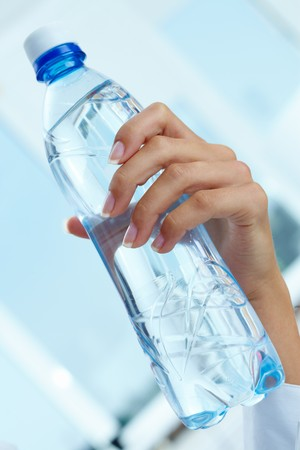 hand holding bottle: Image of plastic water bottle in female hand Stock Photo