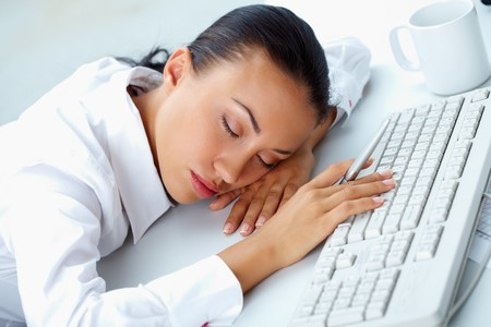 Image of young businesswoman sleeping on workplace with her head on keyboard Stock Photo - 7300182