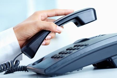 persona llamando: Mano femenina sosteniendo tel�fono receptor sobre telepnone  Foto de archivo