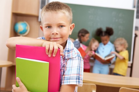 schoolboy: Image of smart schoolboy looking at camera with smile on background of classmates