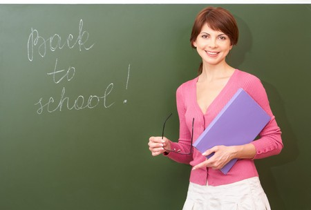 Portrait of young teacher with book and eyeglasses looking at camera by the blackboard Stock Photo - 7306195