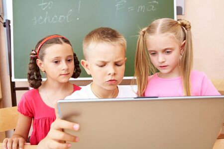 Portrait of schoolboy and two schoolgirls looking at the laptop during lesson  photo