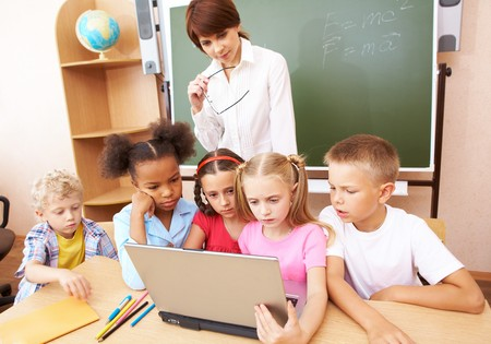 Photo of serious schoolkids and their teacher looking at laptop in classroom photo
