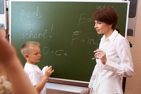 elementary student writing formulae on blackboard with his teacher near by Stock Photo - 7306196