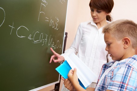additional chemicals:  elementary student holding copybook with his teacher pointing at blackboard Stock Photo