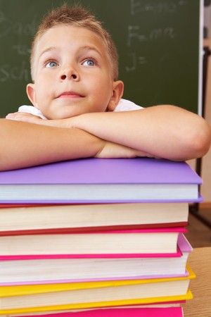 diligent: Face of diligent schoolboy looking upwards with his head on stack of books over black background Stock Photo