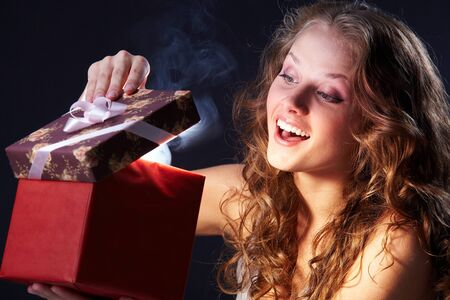 Image of happy girl looking into gift box and wondering photo