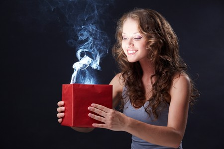 extraordinary: Image of happy girl looking into open gift box and wondering Stock Photo