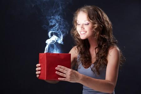 Imagen de chica feliz mirando en caja de regalo abierto y preguntando