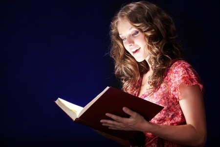 mystery woman: Image of pretty girl looking into open book of magic and reading it