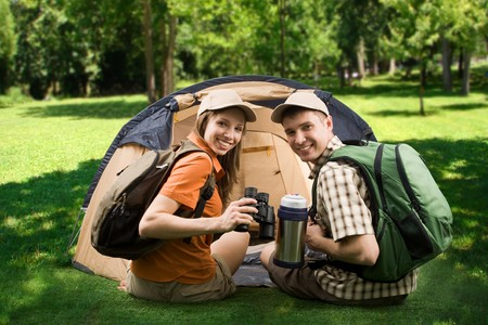 cheerful girl and guy sitting on green grass by tent and looking at camera with smiles photo