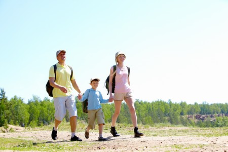 Portrait of three family members walking down road at summer photo