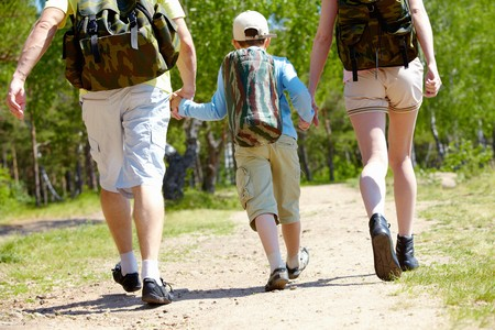 rucksacks: Rear view of three family members going down forest path during summer vacation Stock Photo