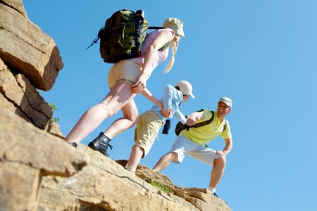 camping: Portrait of happy man helping his wife and son to climb onto high rock Stock Photo