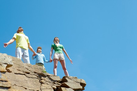 Portrait of family members standing on cliff with stretched arms and enjoying hot day photo