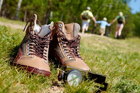 Image of pair of boots and compass on background of happy family running down green grass