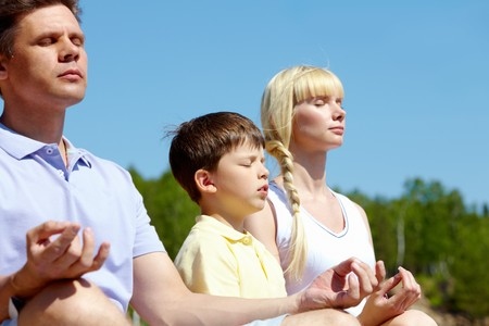 three family members meditating on summer day outdoors photo
