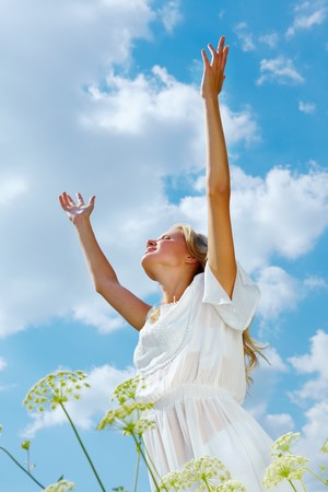 arms raised: Image of happy female standing with raised arms on summer day Stock Photo