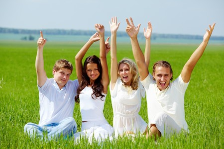 Portrait of happy girls and guys sitting on green grass and raising arms in delight photo