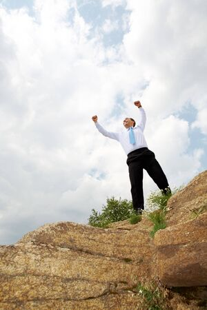Photo of relaxed businessman standing and raising his arms outdoors in summer photo