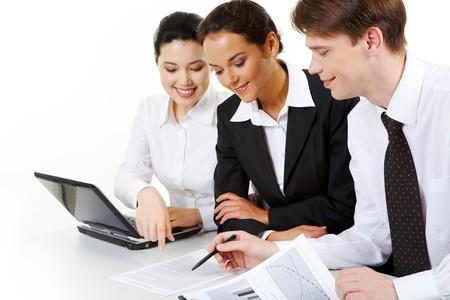 discutere: Ritratto di business team seduti attorno tabella e guardando il documento mentre uomo fiducioso che puntano a questo