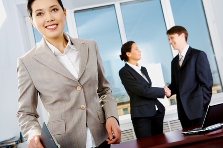 Portrait of beautiful businesswoman in suit on background of handshaking partners photo